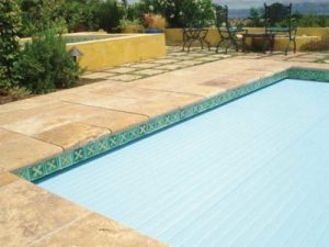 In the traditional mount, if the pool is a skimmer type, the installation specification calls for a stainless steel beam to carry the load of the front of the masonry that is used to conceal the pool cover recess. This beam can be covered with tile to provide a cohesive finish with the cover deploying through a small slot beneath the lid.